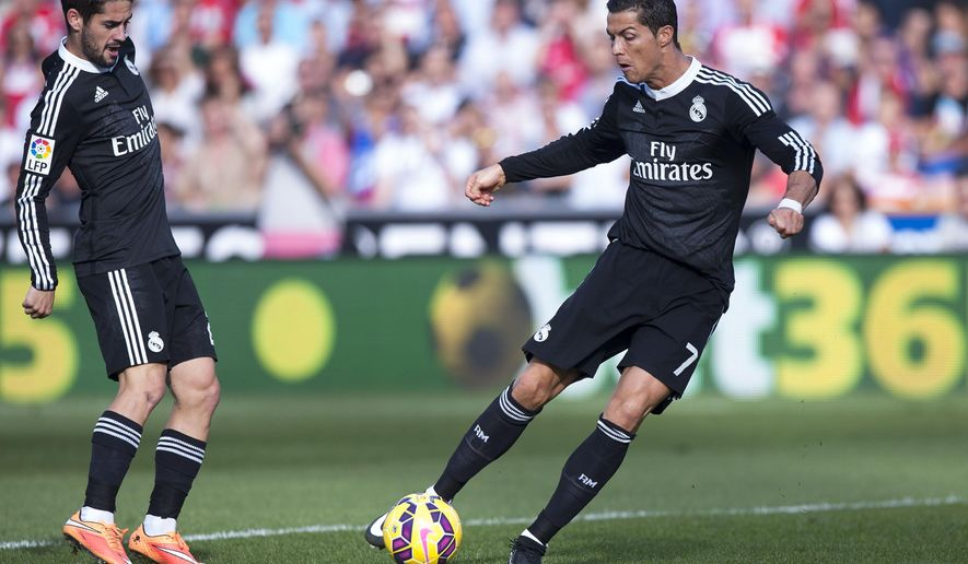 Real Madrid's Cristiano Ronaldo from Portugal, right, kicks the ball during a Spanish La Liga soccer match between Granada and Real Madrid at the Nuevo Los Carmenes stadium in Granada, Spain Saturday Nov. 1, 2014. (AP Photo/Daniel Tejedor)