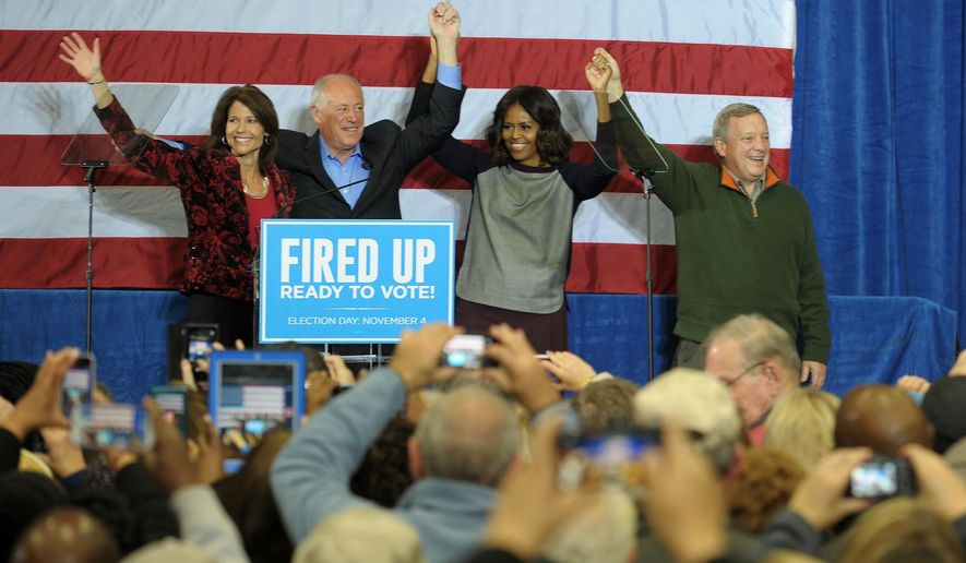 First lady Michelle Obama holds hands during a rally for Illinois Democratic candidates Gov. Pat Quinn, second left, Sen. Dick Durbin, right, and Rep. Cheri Bustos, left, at Wharton Field House in Moline, Ill. on Saturday, Nov. 1, 2014. (AP Photo/The Dispatch, Todd Welvaert)