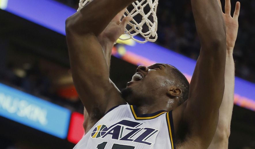 Utah Jazz' Derrick Favors, left, puts a shot up and over Phoenix Suns' Miles Plumlee during the second half of an NBA basketball game in Salt Lake City, Saturday, Nov. 1, 2014. The Jazz defeated the Suns 118-91. (AP Photo/George Frey)