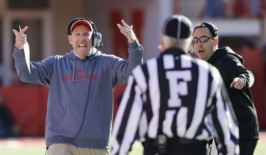 Nebraska head coach Bo Pelini and defensive coordinator John Papuchis, right, dispute a call against Nebraska in the first half of an NCAA college football game against Purdue in Lincoln, Neb., Saturday, Nov. 1, 2014. (AP Photo/Nati Harnik)