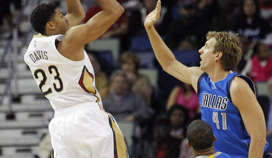 New Orleans Pelicans forward Anthony Davis (23) shoots over Dallas Mavericks forward Dirk Nowitzki (41) in the first half of an NBA basketball game in New Orleans, Saturday, Nov. 1, 2014.  (AP Photo/Bill Haber)