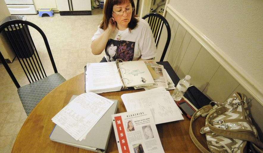 In this Oct. 21, 2014 photo, Stephanie Hanke, stepmother of missing teenager Brittney Wood, looks over materials related to the search for the youth at her home in Mobile, Ala. The teen hasn't been seen since May 2012 and is presumed dead, but 11 relatives and family friends have since been arrested as members of an alleged ring that swapped children for sex. Authorities said Wood could have been a key witness. (AP Photo/Jay Reeves)