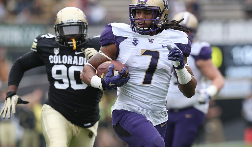 Washington running back Shaq Thompson, front, runs for touchdown past Colorado defensive lineman De'Jon Wilson in the first quarter of an NCAA college football game in Boulder, Colo., on Saturday, Nov. 1, 2014. (AP Photo/David Zalubowski)