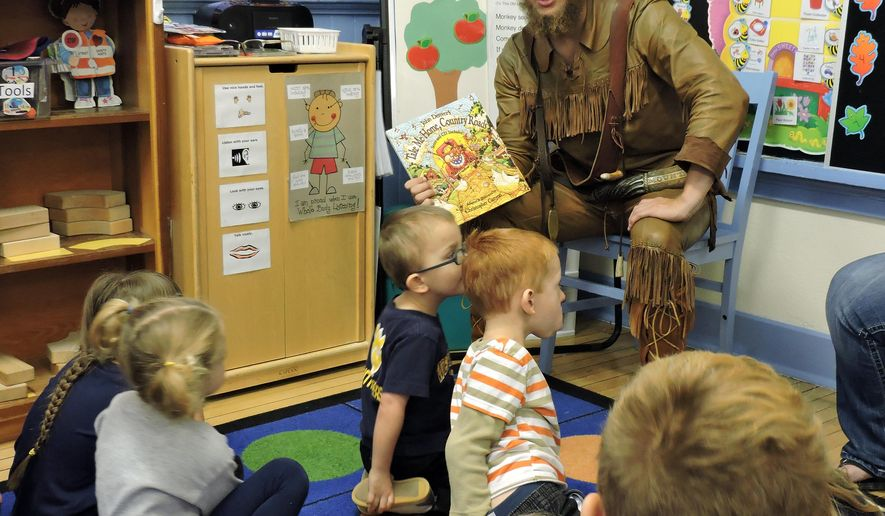 MIchael Garcia reads the children a book that talks about the famous John Denver song Country Roads at Rivesville Head Start, in Rivesville, West Virginia, October 22, 2014. (AP Photo/Times West Virginian, Angelee Wiley)