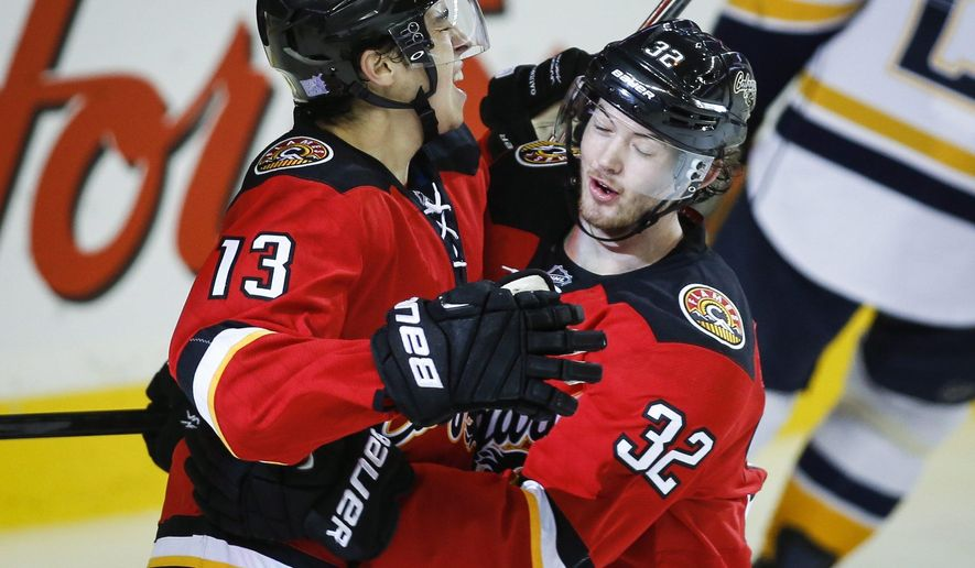 Calgary Flames' Johnny Gaudreau, left, celebrates his goal with teammate Paul Byron during the third period of an NHL hockey game against the Nashville Predators on Friday, Oct. 31, 2014, in Calgary, Alberta. (AP Photo/The Canadian Press, Jeff McIntosh)