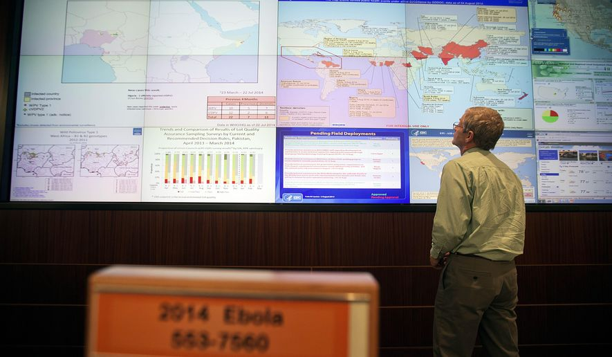 FILE- In this Aug. 5, 2014 file photo, Steve Monroe, deputy director of the National Center for Emerging and Zoonotic Infectious Diseases at the U.S. Centers for Disease Control and Prevention, looks over a map showing global health issues under the agency's surveillance from their Emergency Operations Center in Atlanta. In the space of just a few months, the reputations and approval ratings of the Centers for Disease Control and Prevention, Secret Service, as well as the Veterans Administration, have been seen a decline. (AP Photo/David Goldman, File)