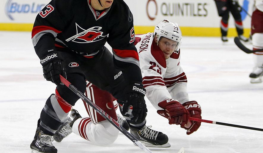 Arizona Coyotes' Oliver Ekman-Larsson (23) of Sweden, reaches in on a charging Carolina Hurricanes' Jeff Skinner (53) during the second period of an NHL hockey game in Raleigh, N.C., Saturday, Nov. 1, 2014. (AP Photo/Karl B DeBlaker)