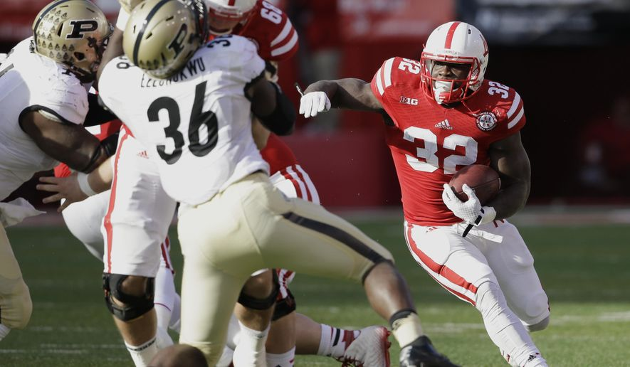 Nebraska running back Imani Cross (32) carries the ball as Purdue linebacker Danny Ezechukwu (36) is blocked by Nebraska offensive lineman Jake Cotton (68) in the first half of an NCAA college football game in Lincoln, Neb., Saturday, Nov. 1, 2014. (AP Photo/Nati Harnik)
