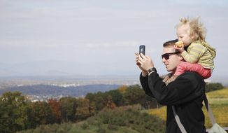 This Thursday, Oct. 30, 2014, photo shows Tom Patterson, 23, from Virginia Beach, and his 21-month-old daughter, Henley, enjoying the views from Carter Mountain Orchard in Charlottesville, Va. Dotted by charming small towns from the mountains to the west and the ocean to the east, Virginia is renewing efforts to tap its natural resources to help drive tourism. While summer remains the peak for tourism, state officials are working to shoulder the busier months with increased tourism other times of the year, especially fall, when leaves change from green to orange, yellow and red. (AP Photo/Michael Felberbaum)