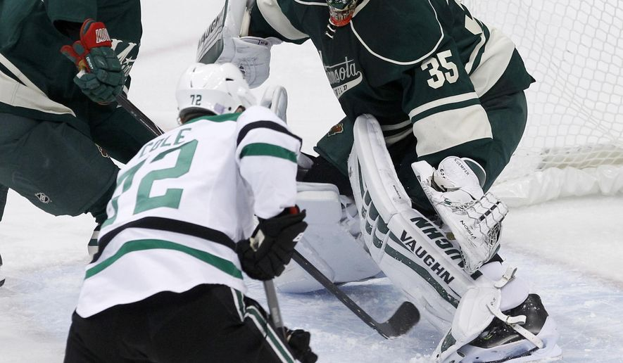 Minnesota Wild goalie Darcy Kuemper (35) deflects a shot in front of Dallas Stars right wing Erik Cole (72) and Wild defenseman Marco Scandella, left, during the first period of an NHL hockey game in St. Paul, Minn., Saturday, Nov. 1, 2014. (AP Photo/Ann Heisenfelt)