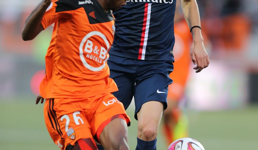 PSG's Edinson Cavani challenges for the ball with Yoann Wachter of Lorient during their League One soccer match in Lorient, western France, Saturday, Nov 1, 2014. Paris Saint germain won 2-1. (AP Photo/David Vincent)