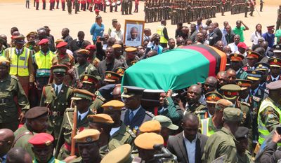 """Members of the Zambian Defence Forces and other government officials attend a ceremony to welcome the body of former Zambian President Michael Sata  at Kenneth Kaunda International Airport in Lusaka, Saturday, Nov,1, 2014. Zambian President Sata dubbed """"King Cobra"""" for his  sharp tongued remarks died in a London hospital Tuesday after a long illness. (AP Photo/Moses Mwape)"""