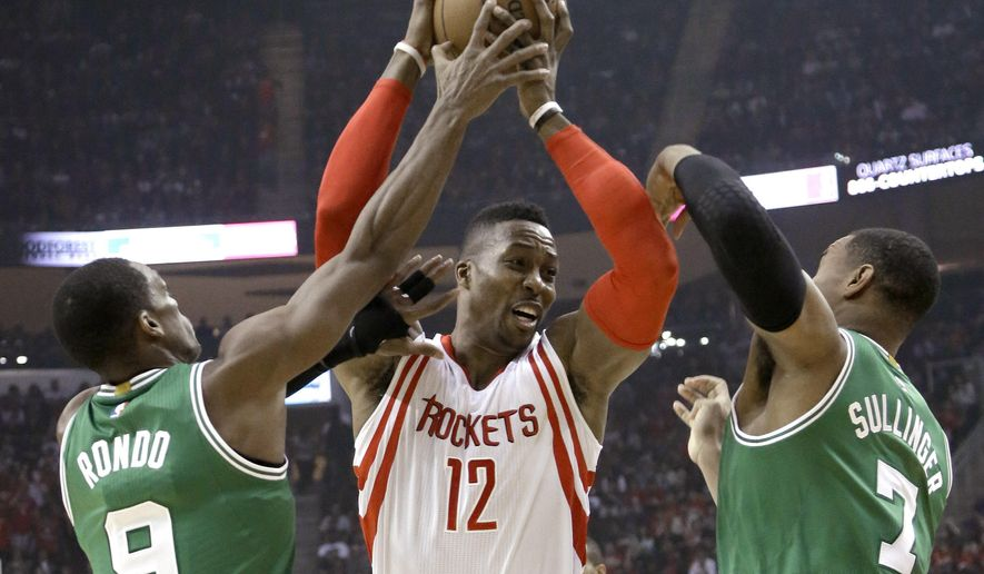 Houston Rockets' Dwight Howard (12) goes to the basket as Boston Celtics Rajon Rondo (9) and Jared Sullinger (7) defend during the first half of an NBA basketball game Saturday, Nov. 1, 2014, in Houston. (AP Photo/Pat Sullivan)