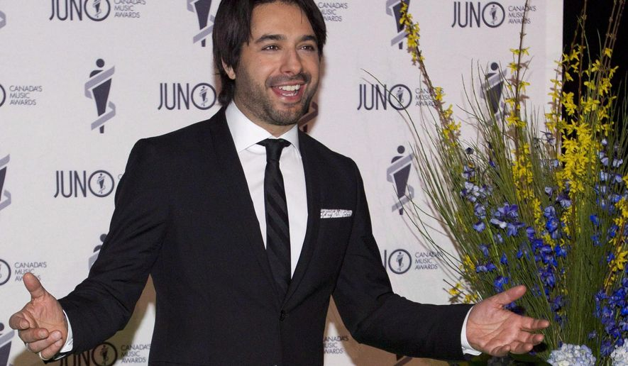 In this March 29, 2014 photo, Jian Ghomeshi arrives on the green carpet for the Juno Gala in Winnipeg, Manitoba. Police are investigating the prominent former Canadian Broadcast Corp. radio host on sexual assault charges after three women came forward to complain. (AP Photo/The Canadian Press, John Woods)