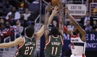 Washington Wizards' John Wall (2) passes the ball as Milwaukee Bucks' Zaza Pachulia (27) and Brandon Knight (11) defend during the first half of an NBA basketball game, Saturday, Nov. 1, 2014, in Washington. (AP Photo/Luis M. Alvarez)
