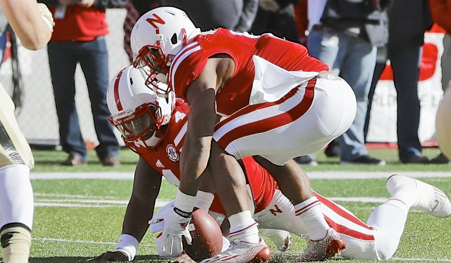 Nebraska running back Ameer Abdullah (8), recovers a ball which was fumbled by quarterback Tommy Armstrong Jr., rear, in the first half of an NCAA college football game against Purdue in Lincoln, Neb., Saturday, Nov. 1, 2014. (AP Photo/Nati Harnik)
