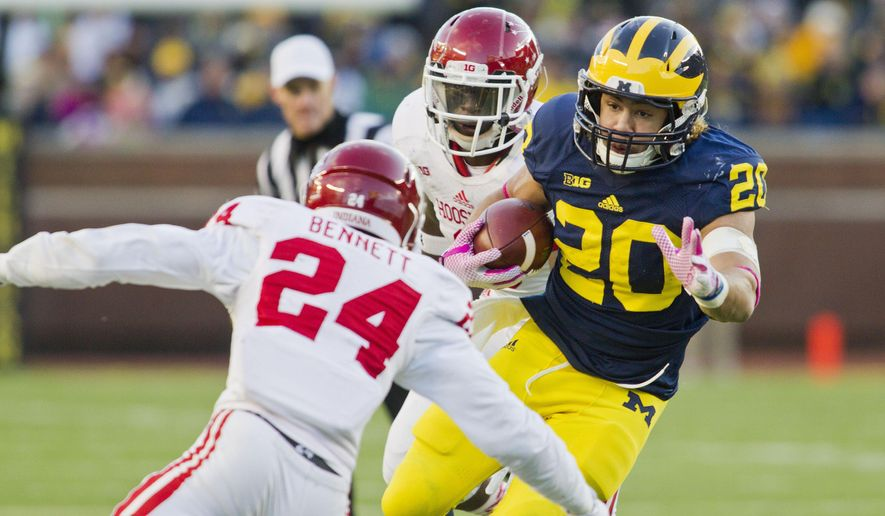 Indiana cornerback Tim Bennett (24) defends against Michigan running back Drake Johnson (20) rushing in the third quarter of an NCAA college football game in Ann Arbor, Mich., Saturday, Nov. 1, 2014. Michigan won 34-10. (AP Photo/Tony Ding)