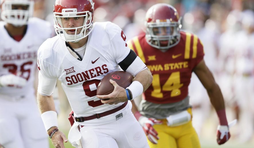 Oklahoma quarterback Trevor Knight runs from Iowa State linebacker Jared Brackens (14) during a 31-yard touchdown run in the first half of an NCAA college football game, Saturday, Nov. 1, 2014, in Ames, Iowa. (AP Photo/Charlie Neibergall)