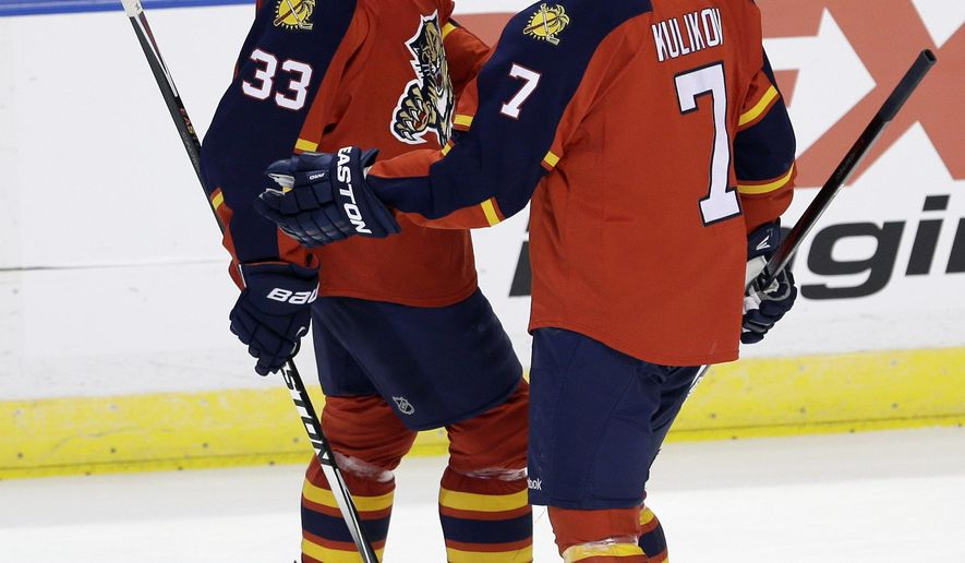 Florida Panthers defenseman Willie Mitchell (33) talks to Dmitry Kulikov (7) after Mitchell  scored against the Philadelphia Flyers in the first period of an NHL hockey game in Sunrise, Fla., Saturday, Nov. 1, 2014. (AP Photo/Alan Diaz)