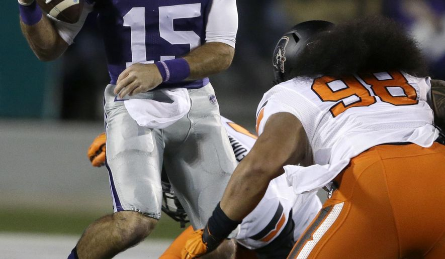 Kansas State quarterback Jake Waters (15) tries to get around Oklahoma State defensive tackle Ofa Hautau (98) during the first half of an NCAA college football game in Manhattan, Kan., Saturday, Nov. 1, 2014. (AP Photo/Orlin Wagner)