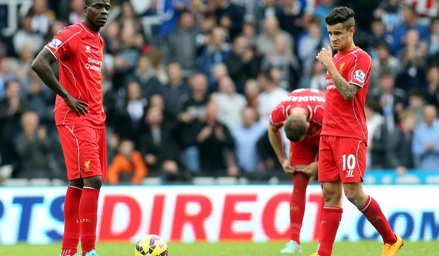 Liverpool's Mario Balotelli, left, and Phillippe Coutinho, right, stand dejected as Newcastle United's Ayoze Perez celebrates his goal during their English Premier League soccer match at St James' Park, Newcastle, England, Saturday, Nov. 1, 2014. (AP Photo/Scott Heppell)