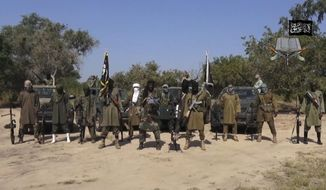 """This image taken from video released late Friday evening, Oct. 31, 2014, by Boko Haram, Abubakar Shekau, centre, the leader of Nigeria's Islamic extremist group denies agreeing to any cease-fire with the government and says more than 200 kidnapped schoolgirls all have converted to Islam and been married off. In the new video released late Friday night, Abubakar Shekau dashed hopes for a prisoner exchange to get the girls released. """"The issue of the girls is long forgotten because I have long ago married them off,"""" he said, laughing. """"In this war, there is no going back,"""" he said in the video received by The Associated Press in the same way as previous messages. (AP Photo/Boko Haram)"""