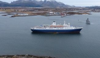 """This image made available by the Royal Norwegian Air Force taken from a rescue helicopter shows a Norwegian coast guard vessel, right, behind the  Bahamas-registered cruise liner """"Marco Polo"""" aground near Gravdal in northern Norway, Saturday Nov. 1, 2014. Passengers had been allowed to leave the cruise ship, which was carrying more than a thousand people when it ran aground in the Lofoten archipelago early Saturday. The same liner also ran aground briefly in a nearby archipelago in March, according to Norwegian media. The cause of that incident remained unclear. (AP Photo/Royal Norwegian Air Force) NORWAY OUT"""
