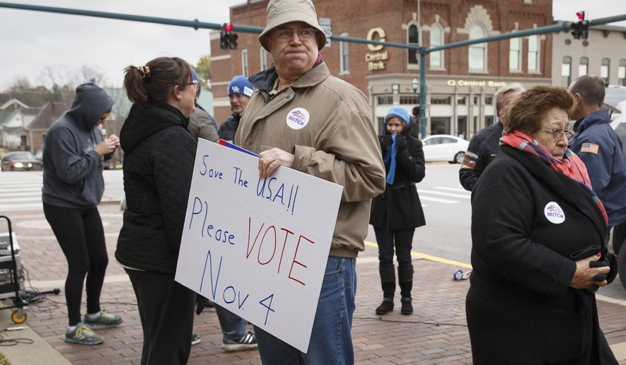John Boone of Lexington, Ky., carries sign urging people to vote on Election Day, as people gather for a political rally for Senate Minority Leader Mitch McConnell, R-Ky., in cold weather on the Scott County Courthouse Square in Georgetown Ky., Saturday, Nov. 1, 2014. (AP Photo/J. Scott Applewhite)