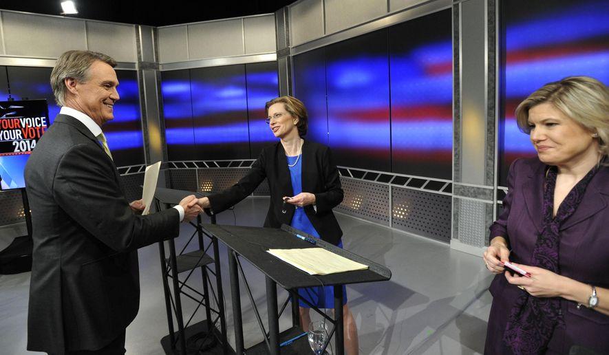 Republican Georgia U.S. Senatorial candidate David Perdue, left, shakes hands with Democrat opponent Michelle Nunn after the final debate of their campaign with Libertarian Amanda Swafford, right, at WSB-TV Sunday, Nov. 2, 2014, in Atlanta. (AP Photo/David Tulis)