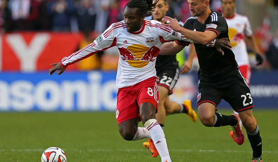 New York Red Bulls forward Peguy Luyindula (8) and D.C. United Perry Kitchen (23) battle for the ball during the first half of an MLS playoff soccer match, Sunday, Nov. 2, 2014, in Harrison, N.J. (AP Photo/Adam Hunger)