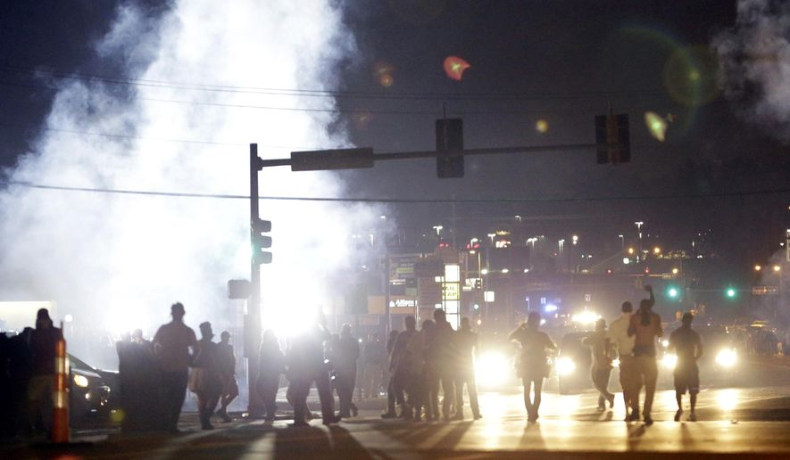In this Monday, Aug. 18, 2014, photo, people stand near a cloud of tear gas in Ferguson, Mo., during protests for the Aug. 9 shooting of unarmed black 18-year-old Michael Brown by a white police officer. (Associated Press)