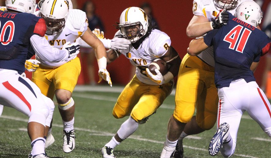 Wyoming's Brian Hill hits the line against Fresno State in the first half of an NCAA college football game in Fresno, Calif., Saturday, Nov. 1, 2014. (AP Photo/Gary Kazanjian)