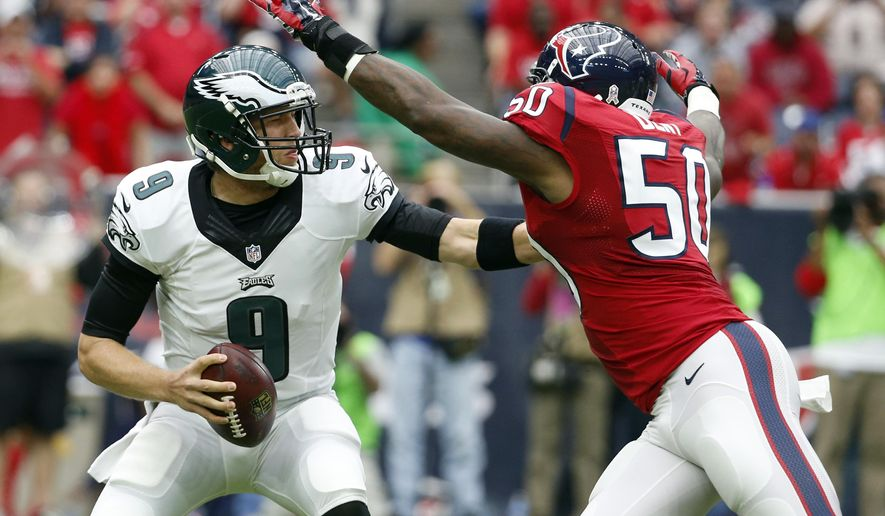 Philadelphia Eagles quarterback Nick Foles, left, scrambles away from Houston Texans linebacker Akeem Dent during the first quarter of an NFL football game, Sunday, Nov. 2, 2014, in Houston. (AP Photo/Tony Gutierrez)