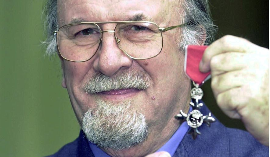 FILE- In this file photo dated March 13, 2001, clarinettist and vocalist Acker Bilk holds his MBE awarded to him for services to the music industry, who has died Sunday Nov. 2, 2014, aged 85. The legendary jazz clarinettist famed for his rendition of 'Stranger on the Shore' in 1962 and made him an international star. (AP Photo / John Stillwell, PA) UNITED KINGDOM OUT - NO SALES - NO ARCHIVES