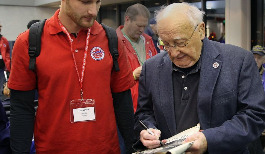 Milwaukee Brewers all-star catcher Jonathan Lucroy watches as WWll veteran Joe Delmer signs a copy of Like Magazine that featured Delmer after he was released from a prison camp, Saturday, Nov. 1, 2014. Lucroy is traveling on the Honor Flight with 41 WWII vets and 47 Korean War vets as well as Lucroy's college roommate Sgt. John Coker Jr., who was injured while serving in Afghanistan. (AP Photo/Milwaukee Journal Sentinel, John Klein)