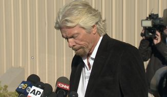 In this video grabbed image, billionaire Virgin Galactic founder Richard Branson, at podium, pauses during a news conference before he saluted the bravery of test pilots, and vowed to find out what caused the crash of his prototype space tourism rocket that killed one crew member and injured another in Mojave, Calif., Saturday, Nov. 1, 2014. (AP Photo/Scott Fain)