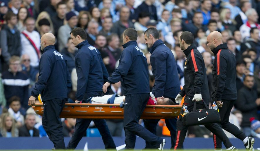Manchester United's Marcos Rojo is carried off the pitch on a stretcher after being injured during his team's English Premier League soccer match against Manchester City at the Etihad Stadium, Manchester, England, Sunday Nov. 2, 2014. (AP Photo/Jon Super)