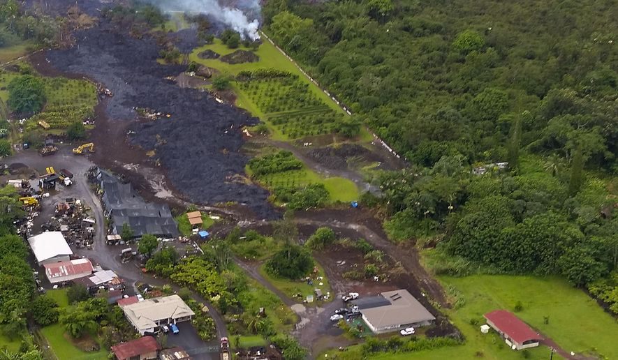 In this Nov. 1, 2014 aerial photo provided by Pete Stachowicz of Paradise Helicopters, lava flows around the town of Pahoa on the Big Island of Hawaii. Lava from Kilauea volcano has stalled just under 500 feet from the main road in Pahoa on the Big Island. Hawaii County Civil Defense said Saturday, Nov. 1, 2014, lava has been breaking out along the sides of the flow that has streamed down the volcano's northeast flank since June. (AP Photo/Pete Stachowicz, Paradise Helicopters)
