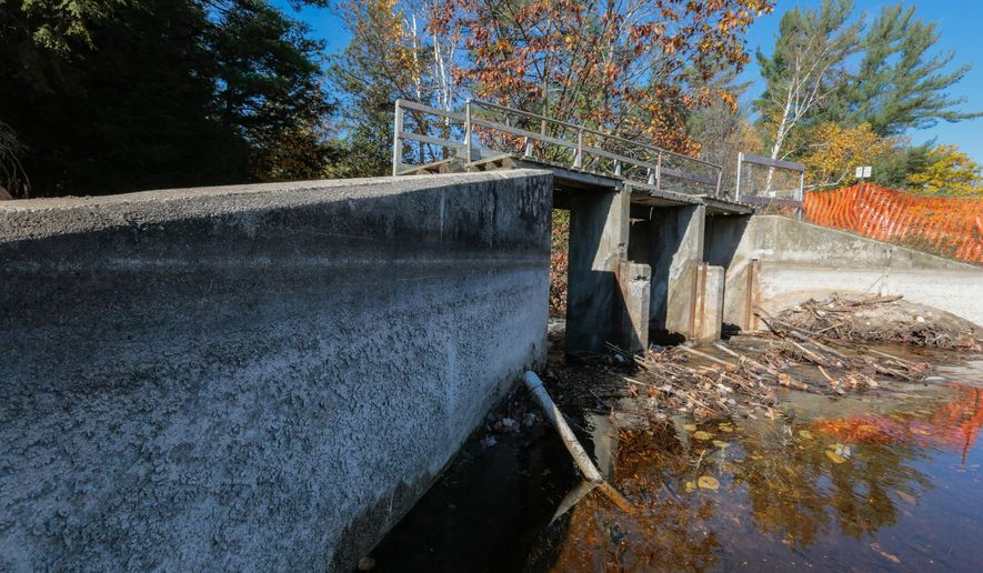 Lines in the cement of O'Neal Lake Dam show previous water levels of O'Neal Lake on Wednesday, Oct. 22, 2014, that were there before a leak in the levee caused by heavy rains went unfixed. (AP Photo/Detroit Free Press, Ryan Garza)