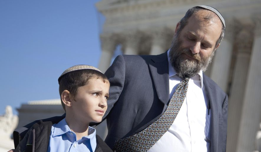 FILE - In this Nov. 7, 2011 file photo, Ari Zivotofsky, right, stands with his nine-year-old son, Menachem, outside the Supreme Court in Washington. The first time Menachem's case was in front of the Supreme Court, Justice Stephen Breyer laid out several reasons why courts should stay out of a dispute between Congress and the president over whether Americans born in Jerusalem may list their place of birth on their passports as Israel. It is back at the high court for argument Monday, Nov. 3, 2014 at a time of acute Palestinian-Israeli tension over Jerusalem and significant strain in Israeli-American relations. (AP Photo/Evan Vucci, File)