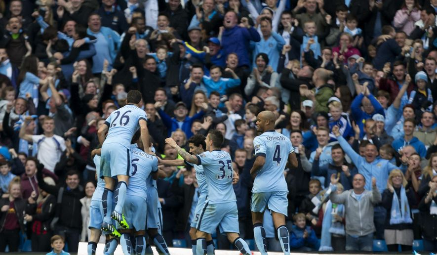 Manchester City's Sergio Aguero, obscured, celebrates with teammates after scoring against Manchester United during their English Premier League soccer match at the Etihad Stadium, Manchester, England, Sunday, Nov. 2, 2014. (AP Photo/Jon Super)