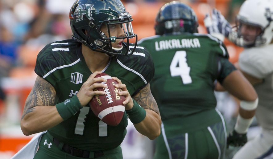 Hawaii quarterback Ikaika Woolsey rolls out to pass while running back Steven Lakalaka (4) looks to block during the first quarter of an NCAA college football game, Saturday, Nov. 1, 2014, in Honolulu. (AP Photo/Eugene Tanner)