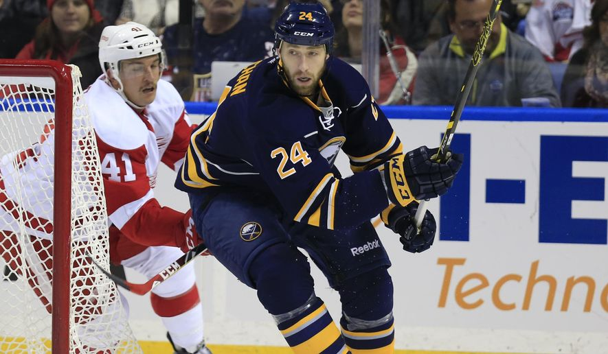 Buffalo Sabres Tyson Strachan (24) tries to move the puck past Detroit Red Wings Luke Gledening (41) during first period action of an NHL hockey game, Sunday, Nov. 2, 2014, in Buffalo, N.Y. (AP Photo/The Buffalo News, Harry Scull Jr)