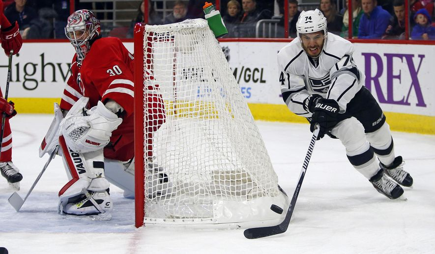 Los Angeles Kings' Dwight King (74) wraps the puck around the net behind Carolina Hurricanes goalie Cam Ward (30) during the first period of an NHL hockey game in Raleigh, N.C., Sunday, Nov. 2, 2014. (AP Photo/Karl B DeBlaker)