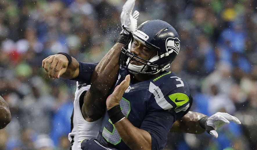 Seattle Seahawks quarterback Russell Wilson reacts after being hit by an Oakland Raiders defensive player after Wilson got a pass off in the second half of an NFL football game, Sunday, Nov. 2, 2014, in Seattle. (AP Photo/Elaine Thompson)