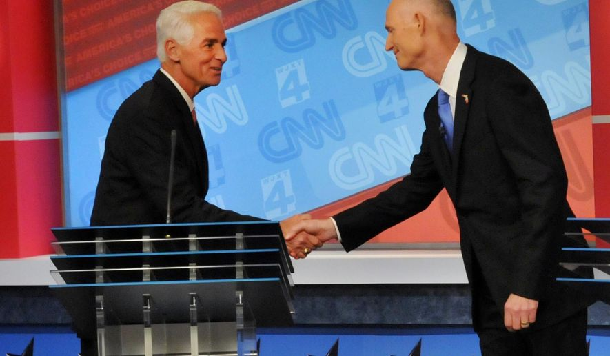 FILE - In this Oct. 21, 2014 file-pool photo, Florida Democratic gubernatorial candidate Charlie Crist, left, shakes hands with Gov. Rick Scott their debate in Jacksonville, Fla. Despite a growing job market and shrinking unemployment, governors are struggling to keep their seats as voters express skepticism about the economic recovery. Wages have stagnated or fallen for many Americans while record numbers of workers hold temporary jobs. Economic malaise, perhaps more than any other factor, is clouding the re-election prospects for governors in both parties.  (AP Photo/The Florida Times-Union, Will Dickey, File-Pool)