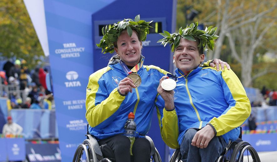 Women's wheelchair winner Tatyana McFadden of the United States, left, and men's wheelchair winner Kurt Fearnley of Australia pose together on the finish line after winning their divisions in the men's wheelchair division of the 44th annual New York City Marathon in New York, Sunday, Nov. 2, 2014.  (AP Photo/Kathy Willens)