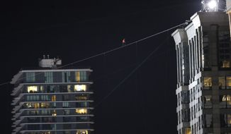 Daredevil Nik Wallenda makes his tightrope walk uphill at a 15-degree angle, from the Marina City west tower across the Chicago River to the top of the Leo Burnett Building, past the Aqua Building, background, Sunday, Nov. 2, 2014, in Chicago. (AP Photo/Charles Rex Arbogast)