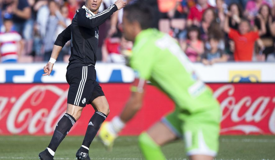 Real Madrid's Cristiano Ronaldo, left, celebrates his goal during a Spanish La Liga soccer match between Granada and Real Madrid at the Nuevo Los Carmenes stadium in Granada, Spain, Saturday, Nov. 1, 2014. (AP Photo/Daniel Tejedor)