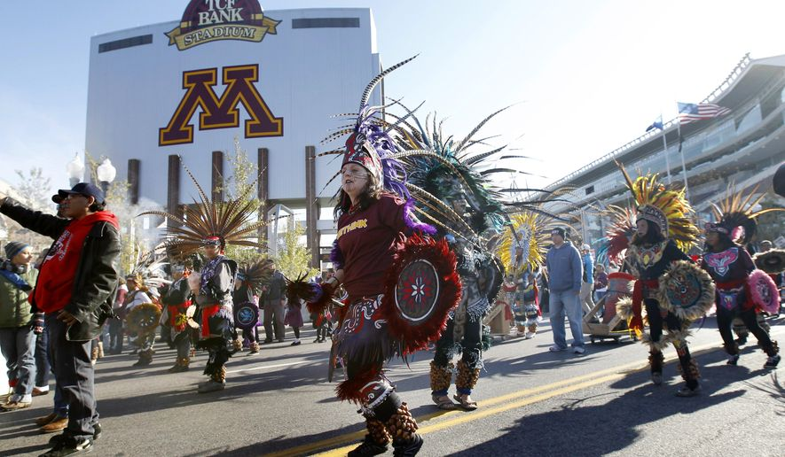 Protestors march outside TCF Bank Stadium before an NFL football game between the Minnesota Vikings and the Washington Redskins, Sunday, Nov. 2, 2014, in Minneapolis. The group was protesting the use of the mascot and name of the Washington Redskins football team. (AP Photo/Ann Heisenfelt)